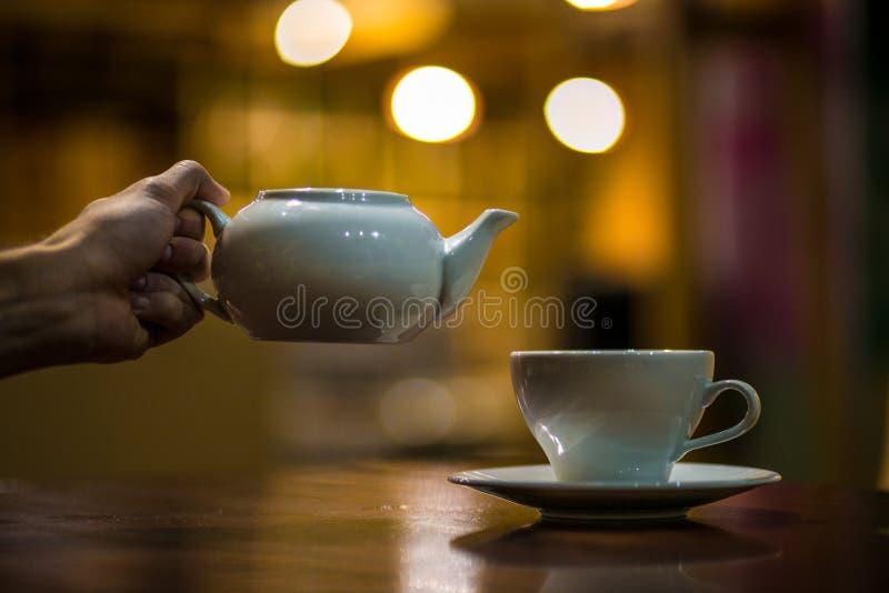 O garçom derrama o chá no copo fotografia de stock royalty free