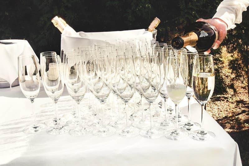 O garçom derrama vidros luxuosos à moda para o champanhe em uma tabela para imagens de stock royalty free