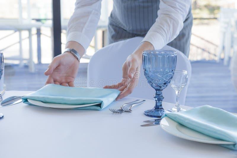 O garçom do restaurante serve uma tabela para uma celebração do casamento fotografia de stock royalty free