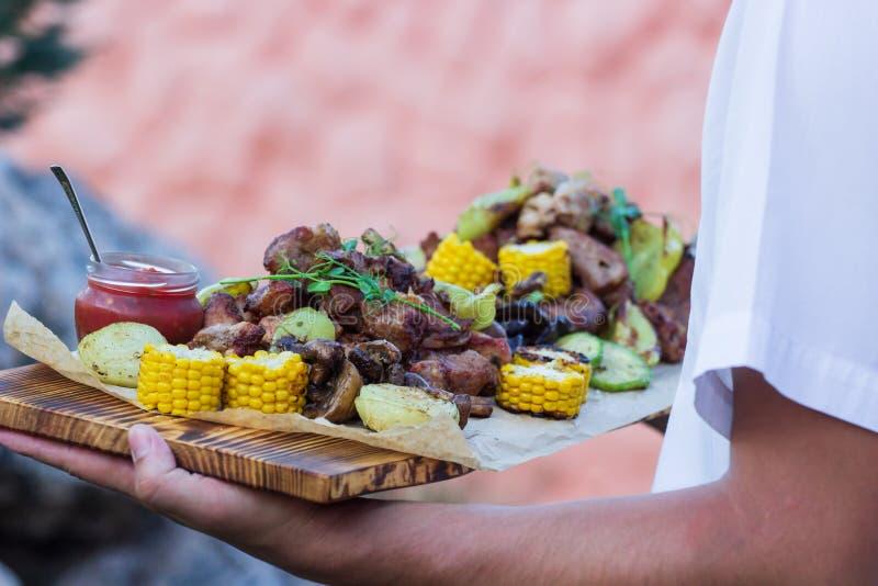 O garçom está oferecendo a carne e vegetais grelhados imagem de stock royalty free