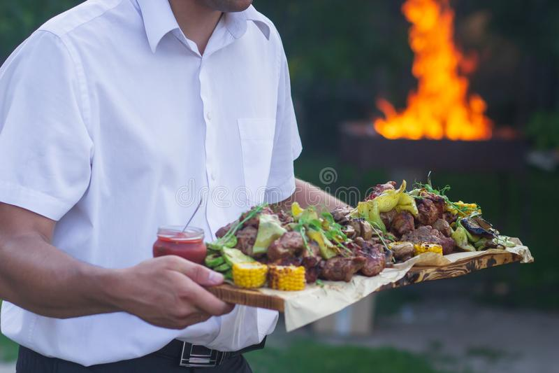O garçom está oferecendo a carne e vegetais grelhados foto de stock