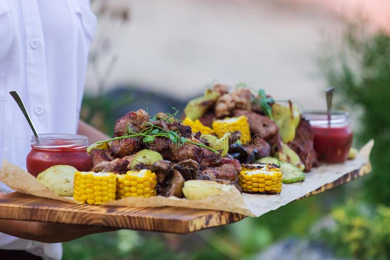 O garçom está oferecendo a carne e vegetais grelhados imagens de stock royalty free