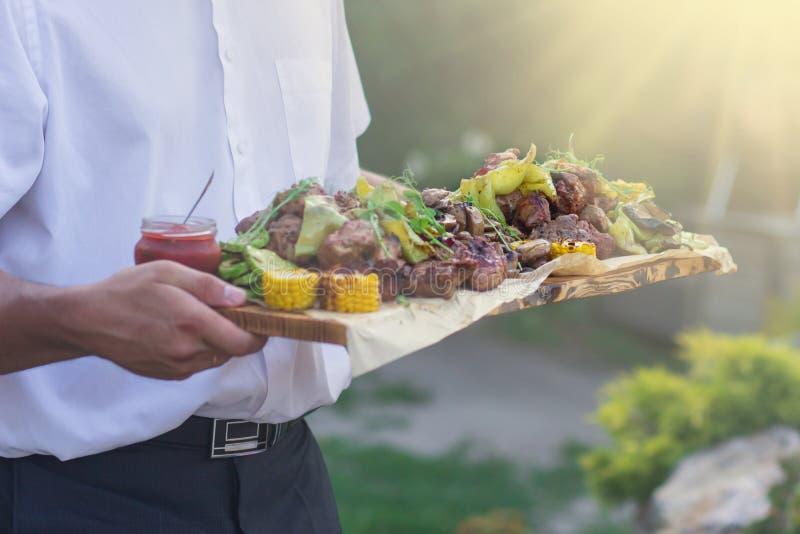 O garçom está oferecendo a carne e vegetais grelhados no dia ensolarado fotos de stock royalty free