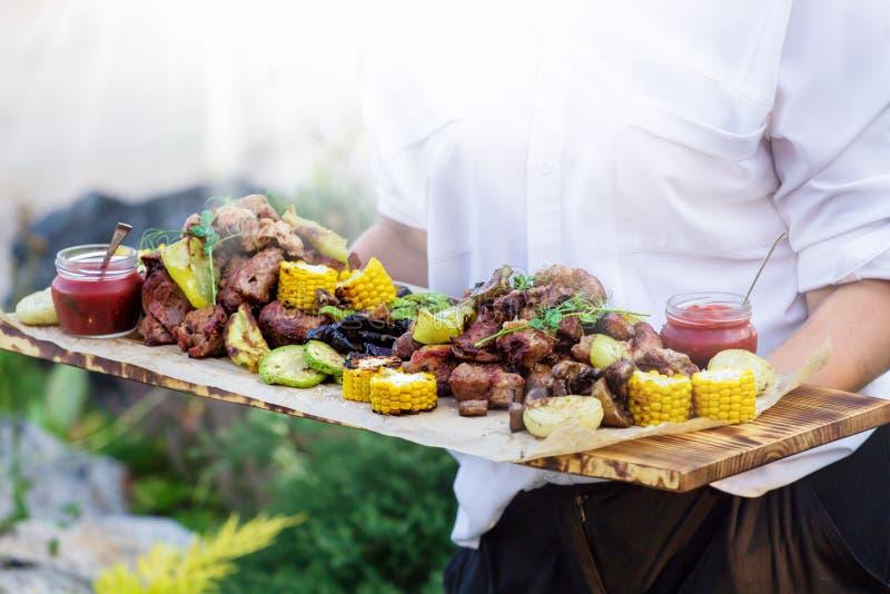 O garçom está oferecendo a carne e vegetais grelhados no dia ensolarado foto de stock
