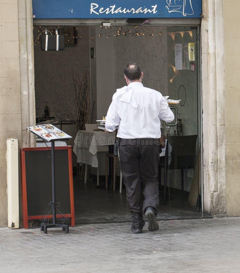 O garçom leva o alimento à cozinha imagens de stock royalty free