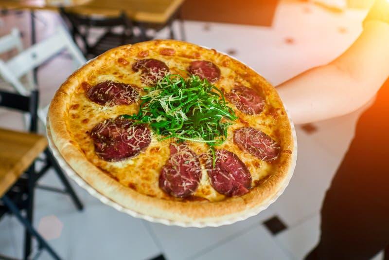 O garçom leva a pizza ao cliente imagem de stock
