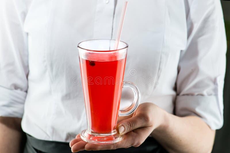 O garçom não identificado traz um cocktail quente do chá do arando com foto de stock