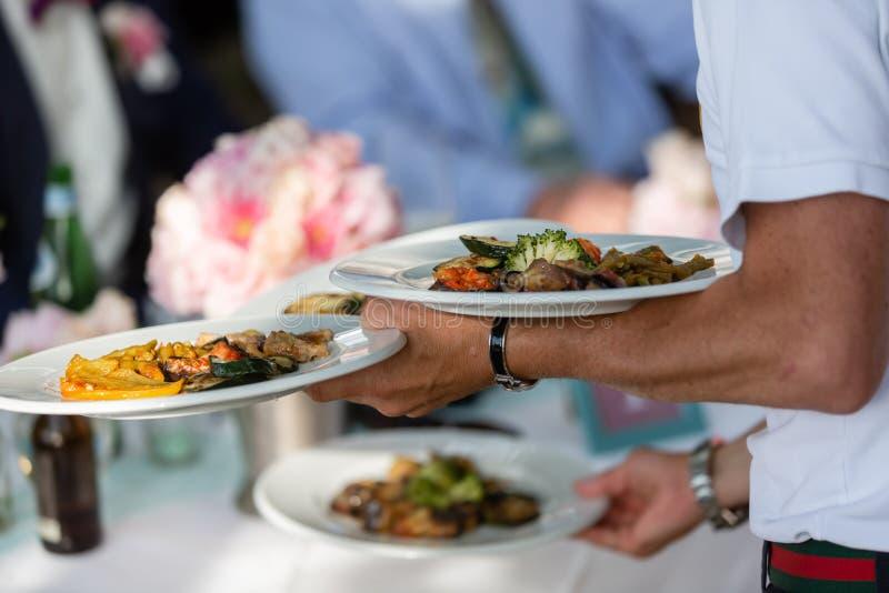 O garçom serve antipasti italianos em um restaurante exterior imagem de stock royalty free