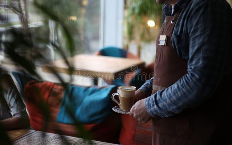 o garçom serve os visitantes, trazidos o café, ordem imagem de stock royalty free