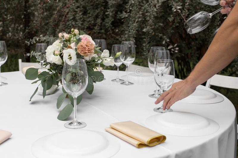 O garçom serve a tabela de banquete Ajuste da tabela do casamento decorado com flores e os castiçal de bronze com velas fotografia de stock royalty free