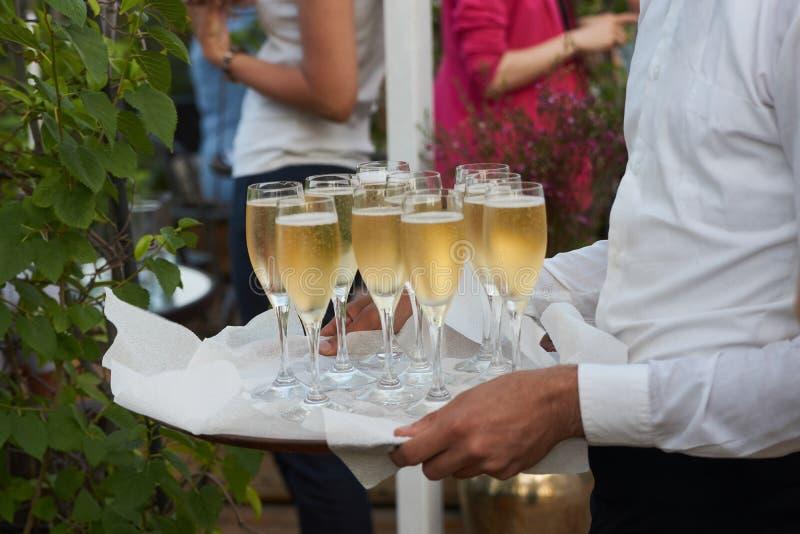 O garçom traz vidros do champanhe em uma bandeja no partido do evento do casamento, close-up imagem de stock