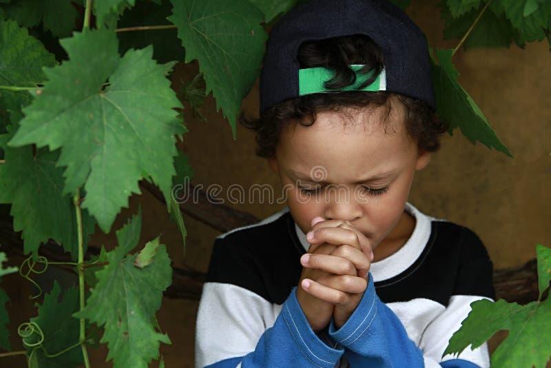 O garotinho rezando para Deus com as mãos juntas. imagens de stock royalty free