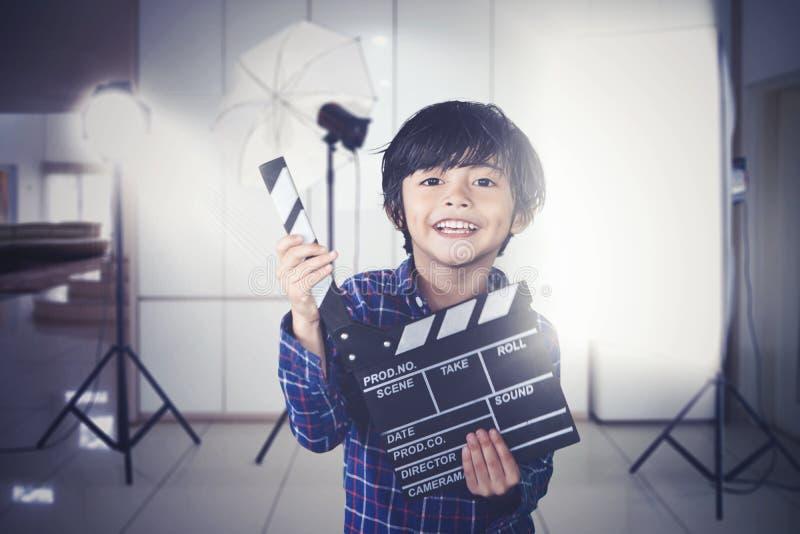 O garotinho segura papelão durante a produção de filmes imagem de stock royalty free