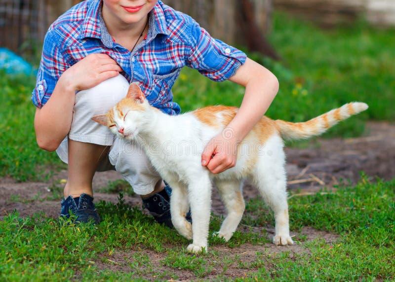 O gato do gengibre fricciona maciamente contra o pé de um rapaz pequeno fotos de stock royalty free