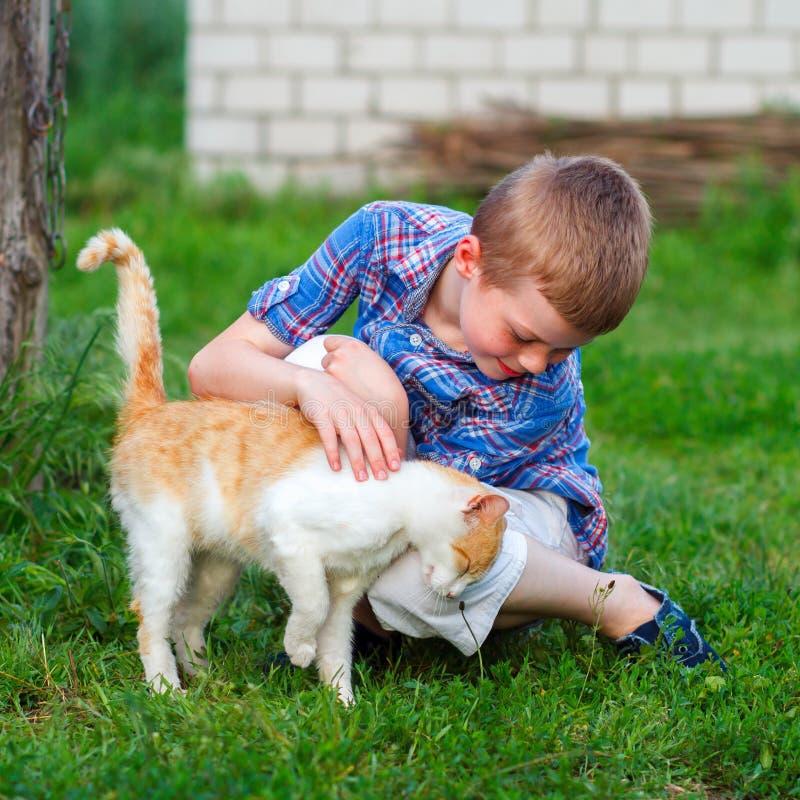 O gato do gengibre fricciona maciamente contra o pé de um rapaz pequeno imagem de stock royalty free