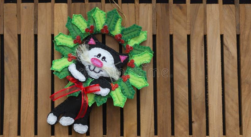 O gato preto no meio de uma coroa das folhas verdes do visco fez em espumoso para a decoração do Natal fotos de stock royalty free