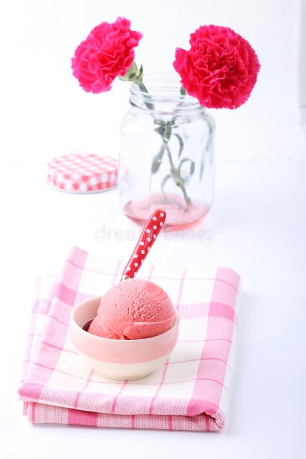O gelado caseiro vermelho de morango e o cravo vermelho florescem fotografia de stock royalty free