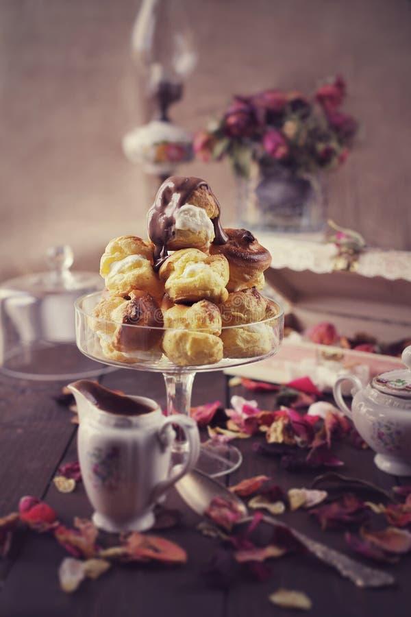 O gelado fresco encheu profiteroles com o molho de chocolate quente fotografia de stock