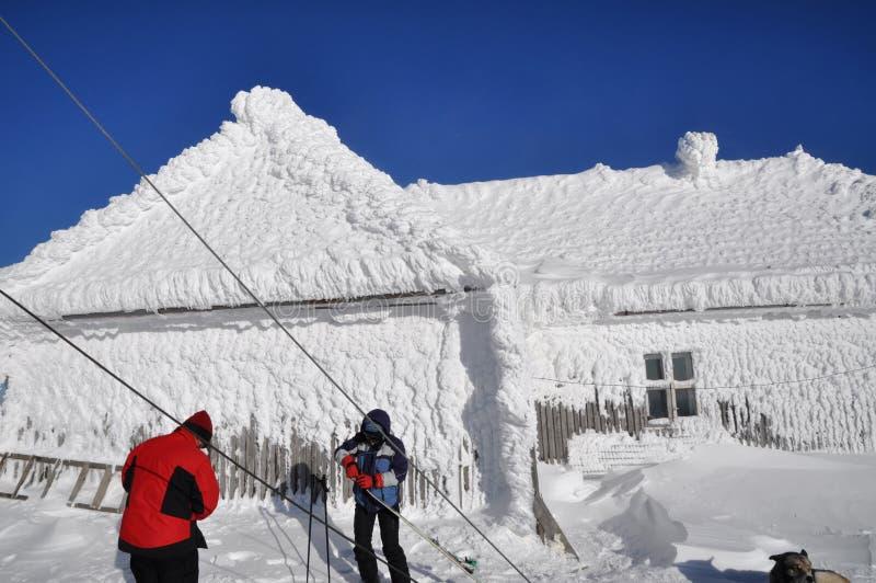 O gelo cobriu a casa nas montanhas imagens de stock royalty free