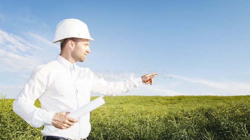 O geodesist do construtor no capacete branco com desenhos aponta o lugar da construção do objeto coordenador na terra para a casa imagens de stock royalty free