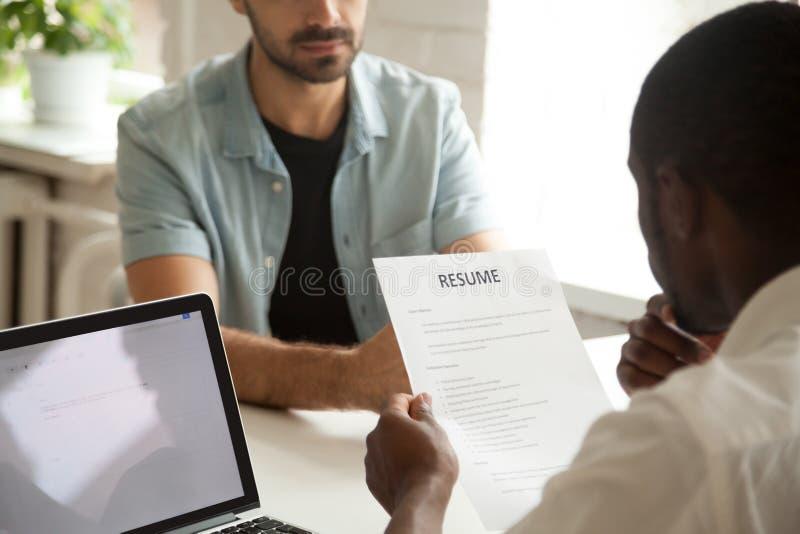 O gerente afro-americano da hora que guarda candidatos da leitura recomeça em fotos de stock royalty free