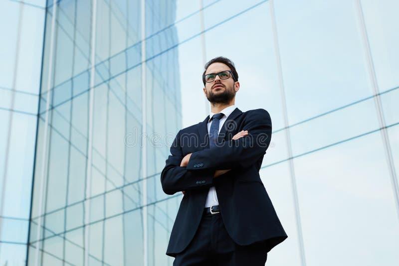 O gerente bem sucedido novo está esperando seu sócio na rua na frente do prédio de escritórios imagem de stock royalty free