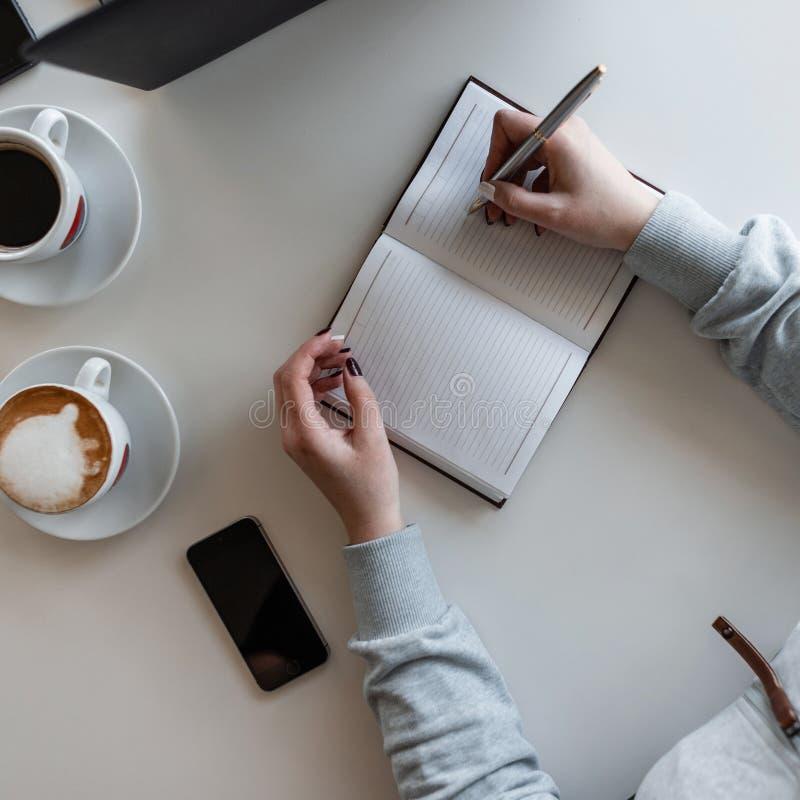 O gerente da mulher senta-se em uma tabela branca em uma reunião de negócios em um escritório moderno com um executivo, escuta-lh imagens de stock