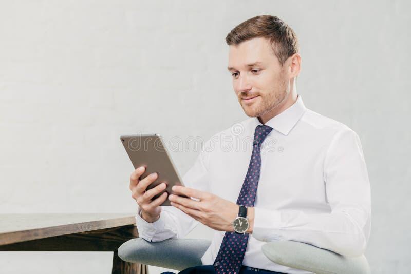 O gerente executivo masculino na camisa branca e o laço, tablet pc das posses, procuram a informação necessária no Internet, cone fotos de stock royalty free