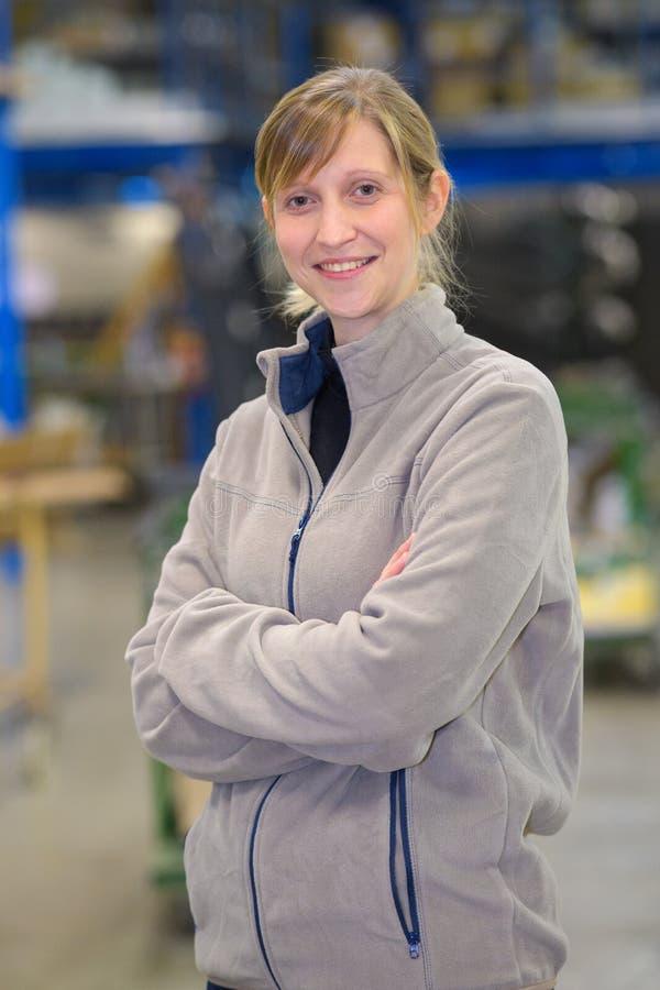 O gerente fêmea de sorriso do retrato com braços cruzou-se no armazém imagens de stock