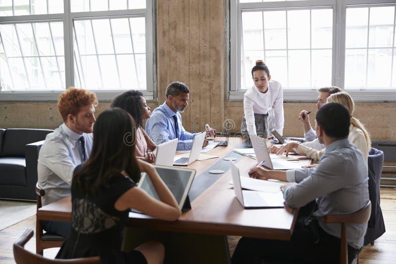 O gerente fêmea inclina-se ao endereçar a equipe na reunião da direção imagem de stock royalty free