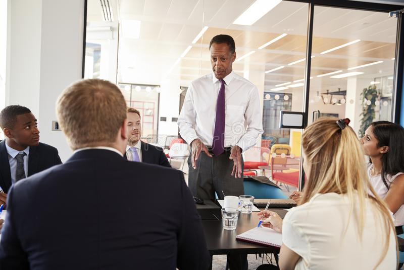 O gerente masculino preto está de fala em uma reunião de negócios imagens de stock royalty free