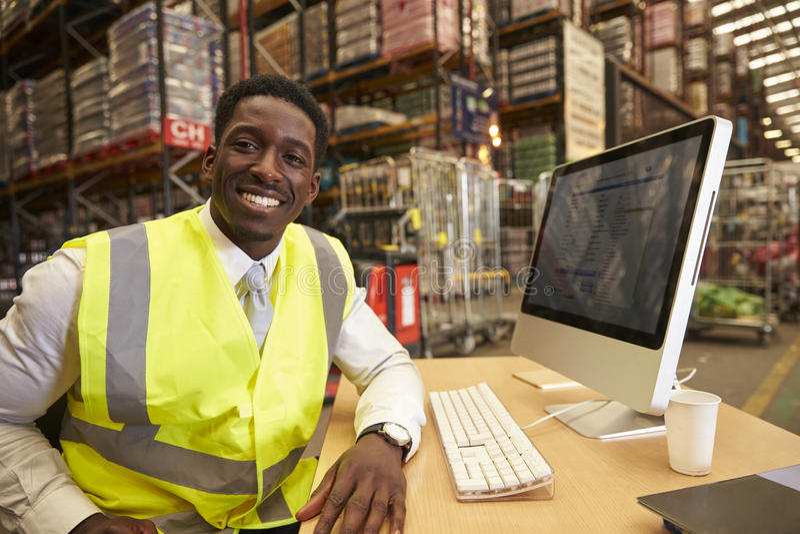 O gerente no escritório no local de um armazém olha à câmera fotos de stock