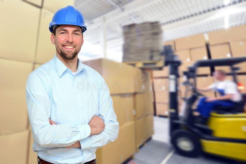 O gerente trabalha no local no armazém de uma empresa industrial imagens de stock royalty free