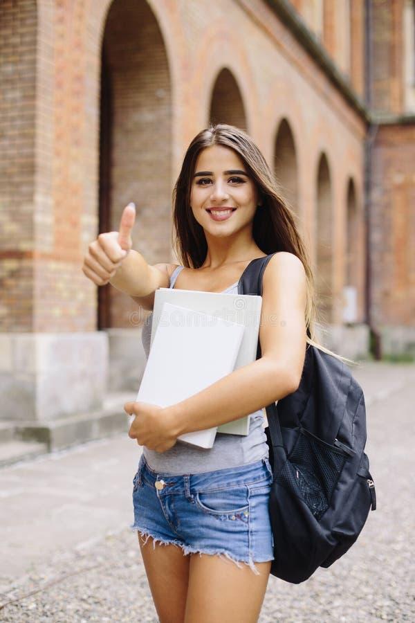 O gesto da aprovação da mostra da menina que estuda na universidade é bom imagem de stock royalty free