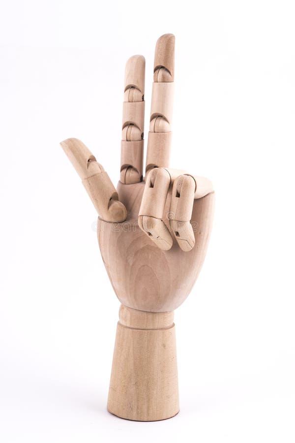 O gesto do número três fez com uma mão de madeira articulada imagens de stock