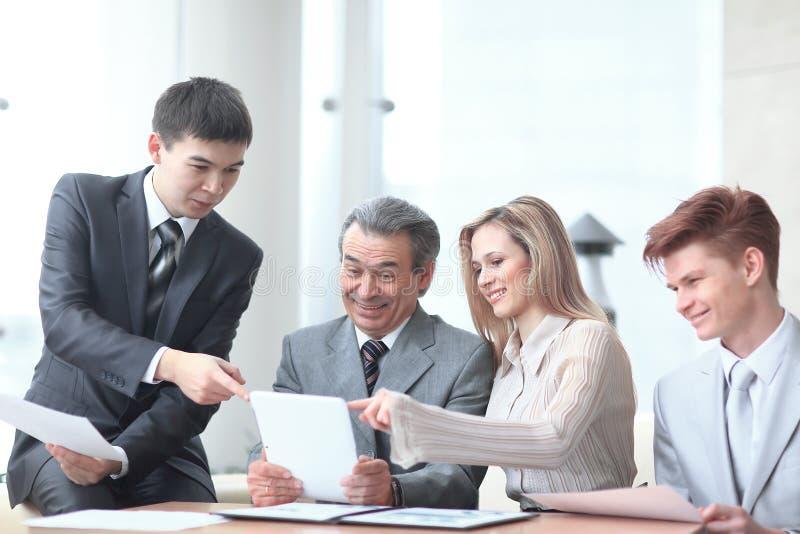 O gestor de projeto e a equipe do negócio usam uma tabuleta digital para obter a informação operacional imagens de stock royalty free