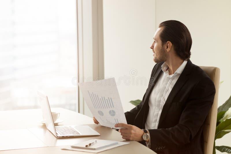 O gestor de projeto pensativo no escritório está guardando o relatório financeiro foto de stock