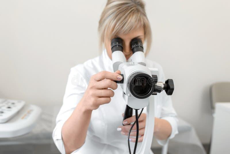 O ginecologista profissional fêmea novo no processo de trabalho, olha no colposcope foto de stock
