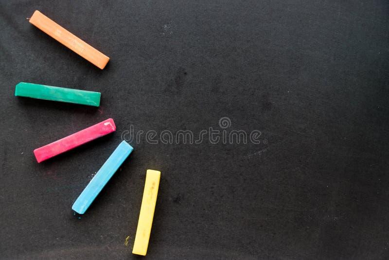O giz colorido no fundo preto da placa com espaço da cópia para adiciona foto de stock royalty free