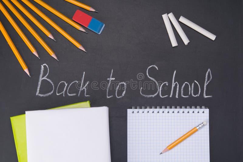 O giz no quadro-negro, de volta à escola, um grupo de lápis e um eliminador, há um lugar para escrever em um bloco de notas branc fotos de stock