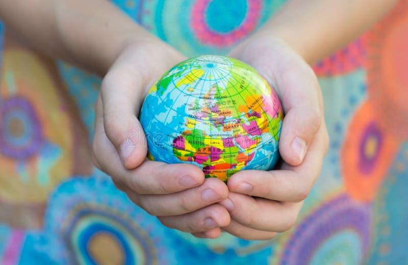 O globo azul com os territórios dos países do mundo em um fundo colorido, imagem de stock