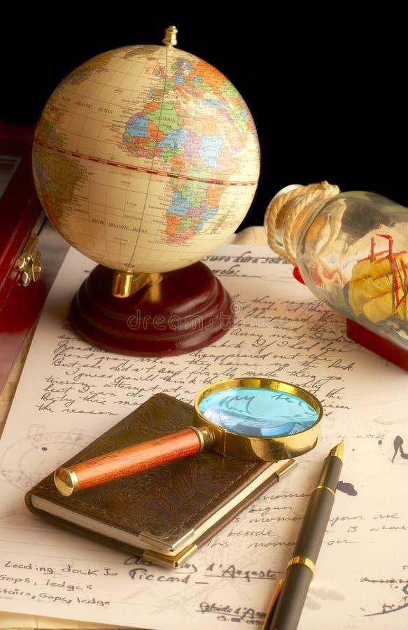 O globo, magnifier com um caderno e o manuscrito velho imagem de stock royalty free
