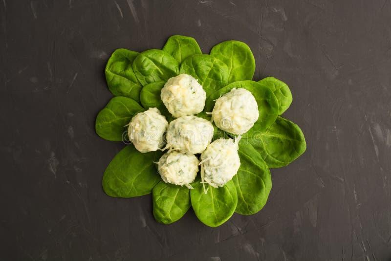 O gnocchi cozinhado sobre espinafres frescos verdes sae com o queijo, liso imagem de stock