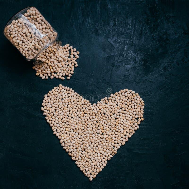 O grão-de-bico ou os grãos-de-bico secados saudáveis derramaram o frasco de vidro, coração deram forma aos feijões crus orgânicos imagens de stock royalty free