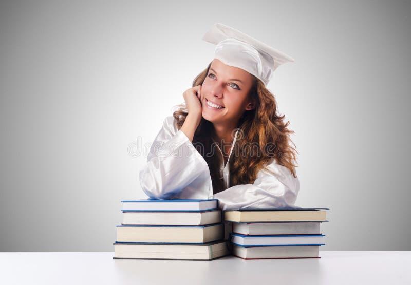 O graduado feliz com lotes dos livros no branco fotos de stock