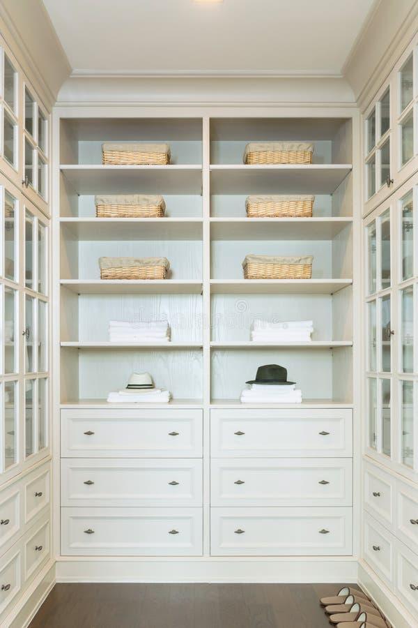 O grande armário de pessoas sem marcação branco com prateleiras fotografia de stock