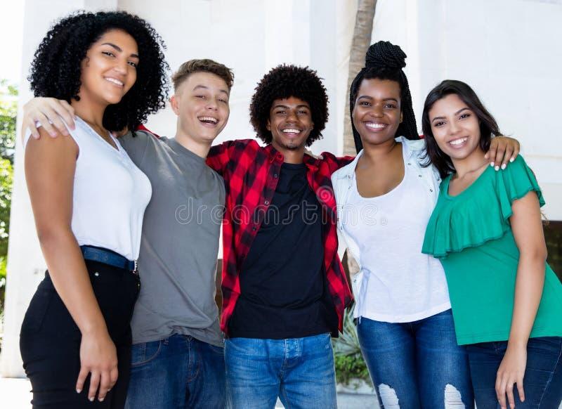 O grande grupo de adultos novos brasileiros arma-se no braço foto de stock