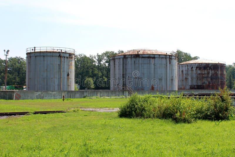 O grande metal três oxidou os silos do armazenamento cercados com muro de cimento e vegetação de floresta imagens de stock