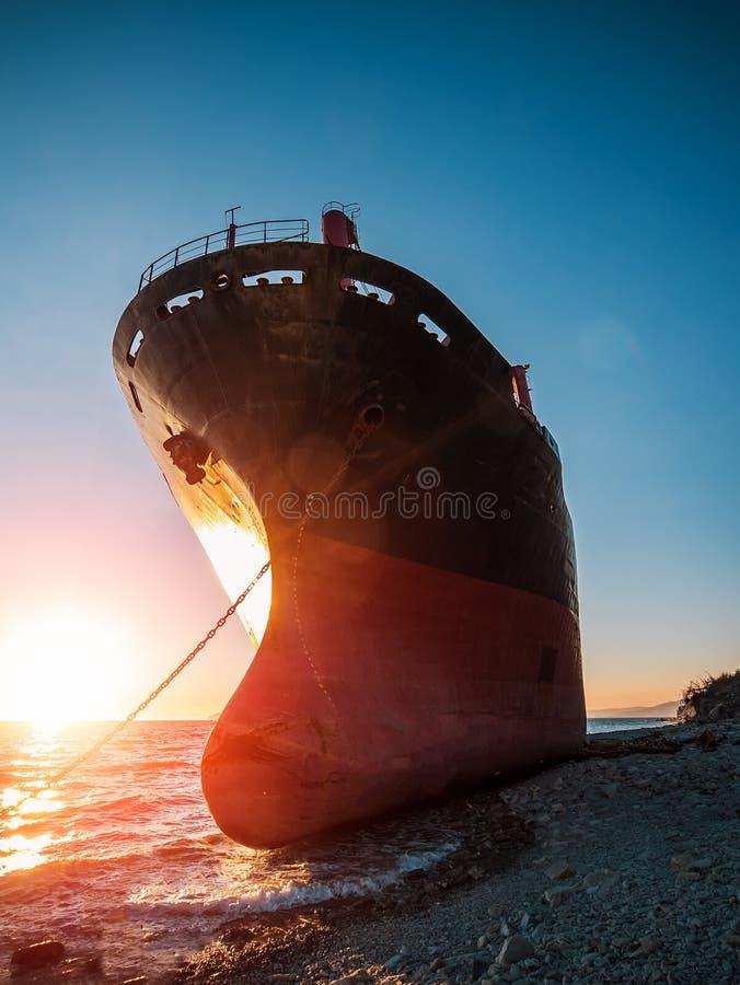 O grande navio de carga do ferro corre encalhado na baía do mar no por do sol Naufrágio industrial da embarcação do mar no litora imagens de stock royalty free