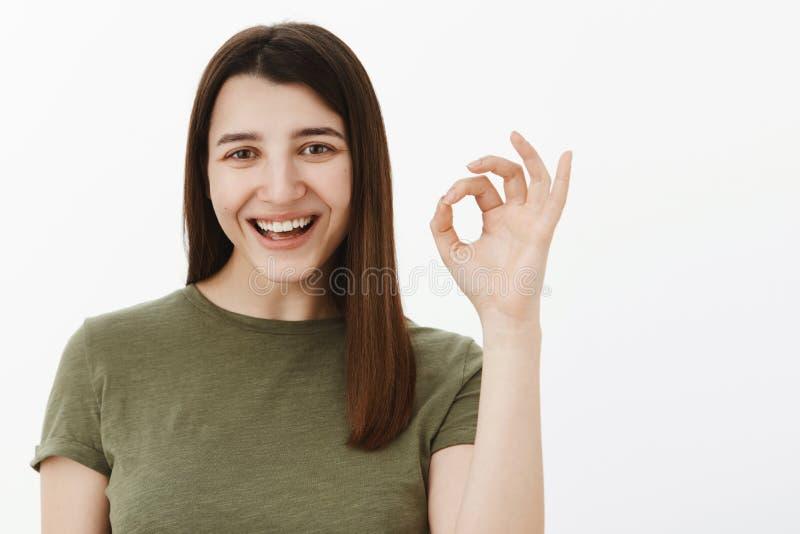 O grande negócio, confirma-o Morena europeia otimista feliz e despreocupada no sinal e no sorriso verde-oliva da aprovação da exi fotografia de stock royalty free